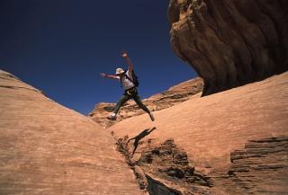sejour-montagne-escalade-jordanie-randonneur-sautant-par-dessus-un-siq-etroit-mais-profond_mv